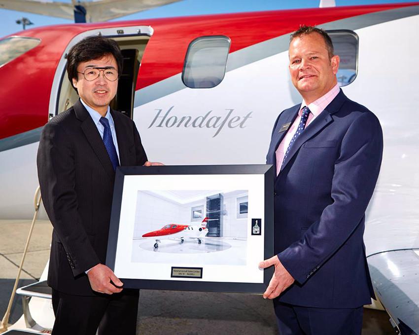 Howard Povey, Head of Aircraft Sales, Northern Europe, Marshall Aviation Services, accepts the keys to HondaJet M-HNDA, registered in the Isle of Man, from Michimasa Fujino, President and CEO of Honda Aircraft Company.